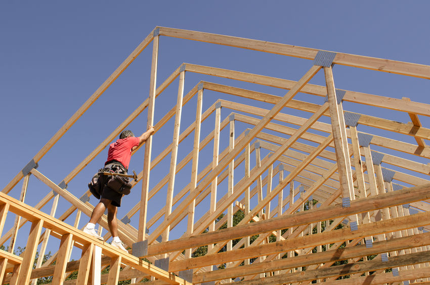 A Building Contractor Placing Trusses On a New Home Construction.
