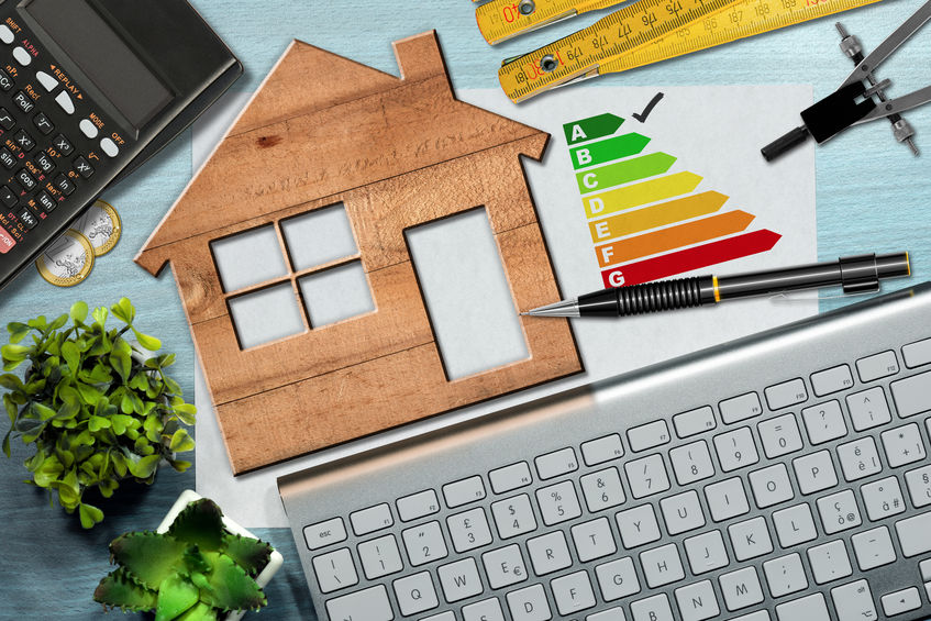 Energy efficiency rating graph on a desk with a wooden house model, calculator, folding ruler, drawing compass, pencil and a computer keyboard